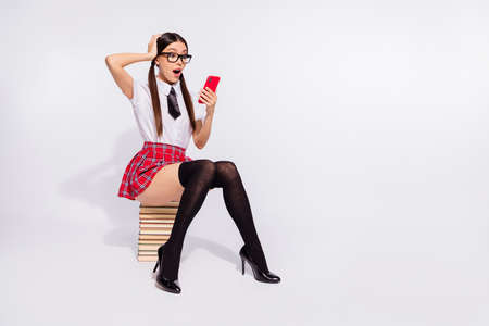 Full length body size photo beautiful she her model teacher sit book pile lesson time texting telephone unexpected news wear specs red checkered costume pantyhose tights isolated white background