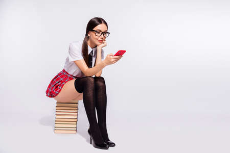 Full length body size photo beautiful she her teacher sit book pile spend lesson time internet boredom texting telephone wear specs red checkered costume pantyhose tights isolated white background