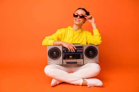 Portrait of dreaming lady touching eyewear eyeglasses sitting with boom box isolated over orange background
