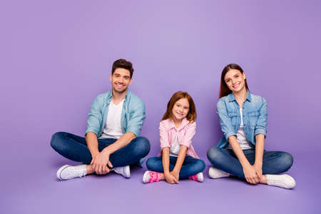 Family of three members sitting floor enjoy best company wear casual clothes isolated purple background