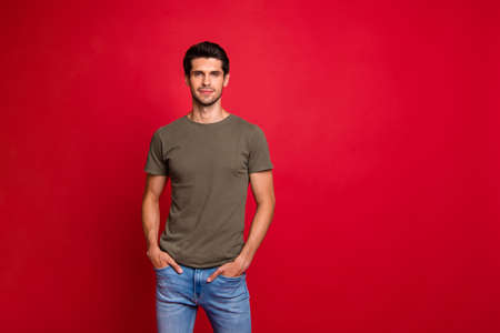 Photo of amazing guy hold hands pockets wear casual grey t-shirt isolated on red background