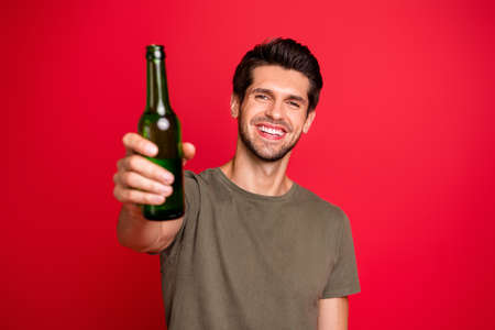 Photo of amazing guy with green beer ale bottle spending great time wear casual grey t-shirt isolated on red background Stock Photo
