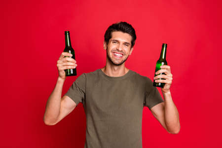 Photo of amazing guy with two green beer ale bottles having great time wear casual grey t-shirt isolated on red background