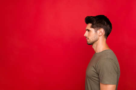Profile photo of macho guy looking empty space wear grey t-shirt isolated on red background