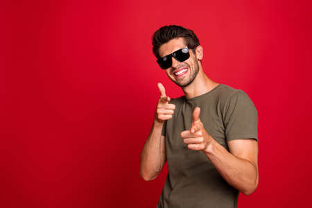 Cool guy indicating fingers I pick you signal wear grey t-shirt isolated on red background