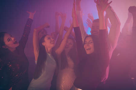 Company of nice-looking attractive smart pretty stylish glad positive excited ladies gentleman having fun rising hands up rejoicing at new cool luxurious modern bar place indoors