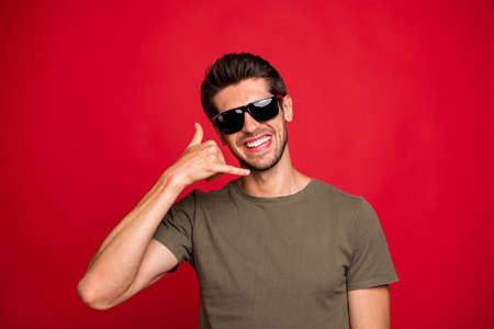 Amazing guy speaking over imaginary telephone with clients wearing casual grey t-shirt isolated on red background