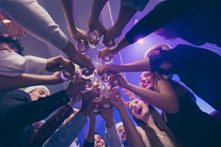 Low below angle view of nice attractive cheerful cheery girls and guys having fun rest relax clinking wineglass congrats corporate event feast celebratory in luxury place nightclub lights indoors Stock Photo