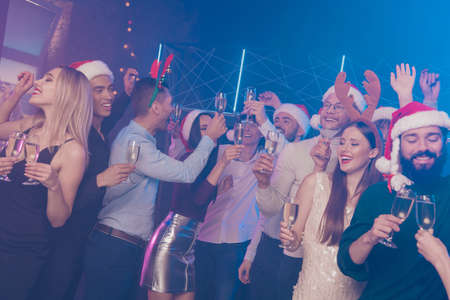 Portrait of nice-looking attractive glamorous gorgeous cheerful cheery funny positive girls and guys having fun nightlife winter December tradition in luxury place nightclub Stock Photo