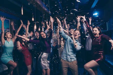 Nice attractive lovely smart glamorous stylish fashionable cheerful glad ecstatic positive girls and guys having fun chill out bachelor graduate festive event tradition in luxury place nightclub