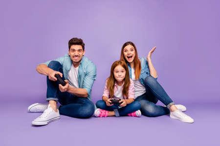 Photo de trois membres de la famille assis au sol essayant dur de gagner le jeu d'équipe porter des vêtements décontractés fond violet isolé