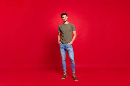 Full length photo of macho guy hold hands pockets street look wear casual outfit isolated on red background