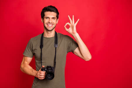 Cool guy with photo digicam showing okey symbol had tested new camera wear t-shirt isolated on red background
