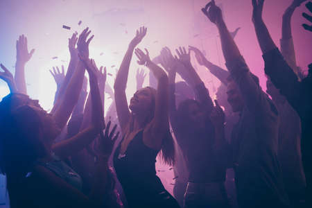 Photo of many birthday event people dancing purple lights confetti flying enjoy nightclub hands raised formal wear outfit