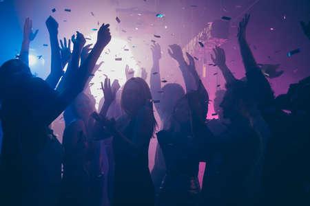Foto ravvicinata di molte persone in festa che ballano coriandoli di luci viola che volano ovunque le mani dell'evento in discoteca si alzano indossano abiti luccicanti Archivio Fotografico