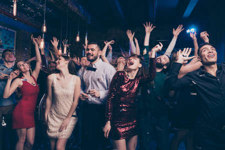 Portrait of charming attractive millennial motion having scream shout rejoice raise hands free time indoors discotheque dress suit formalwear hairstyle Stock Photo