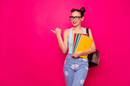 Beautiful lady holding copybooks hands indicating finger empty space wear specs casual outfit isolated pink background