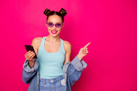 Pretty lady with smart phone indicating finger on banner wear specs casual outfit isolated bright pink background Stock Photo