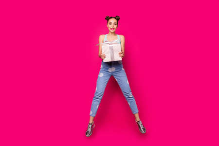 Photo of cute lady holding large giftbox hands jumping high wear casual outfit isolated pink background