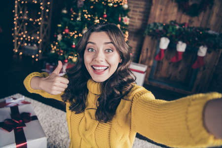 Self photo of nice cute charming good festive attractive beautiful girl thumbing up while standing in front of christmas tree and wearing yellow sweater