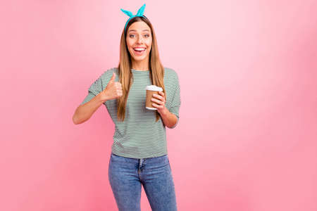 Pretty lady holding hot beverage raising thumb up wear striped pullover isolated pink background