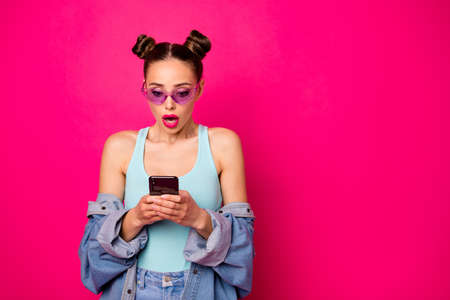Pretty lady hold telephone hands read unexpected news wear sun specs casual outfit isolated bright pink background Stock Photo