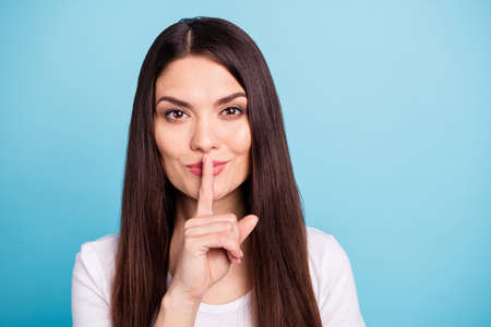 Close up photo of nice cute charming woman showing you shh sign while isolated over blue background
