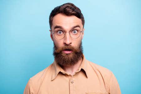 Cerrar foto de hombre encantador mirando vistiendo camisa marrón aislado sobre fondo azul. Foto de archivo