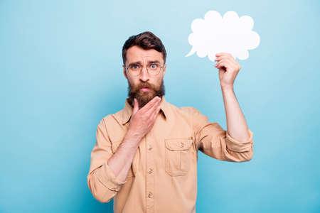 Retrato de hombre de mente en anteojos de gafas sosteniendo la burbuja de la tarjeta de papel tocando su barbilla con camisa marrón aislado sobre fondo azul.