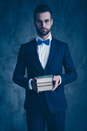 Portrait of charming college man holding paper books having eyewear eyeglasses wearing blue bowtie isolated over gray background Banque d'images