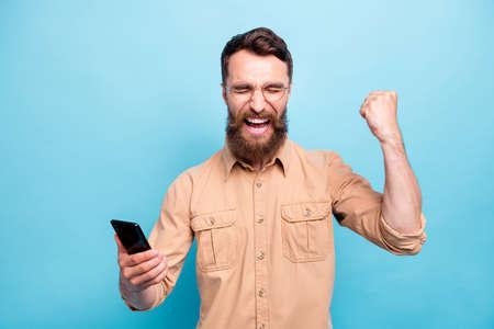 Porträt eines ekstatischen Kerls mit geschlossenen Augen, der seine Fäuste schreit und schreit, trägt braunes Hemd isoliert auf blauem Hintergrund