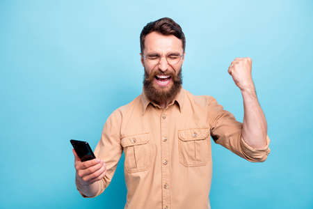 Portrait of ecstatic guy with closed eyes raising his fists screaming yeah wearing brown shirt isolated over blue background