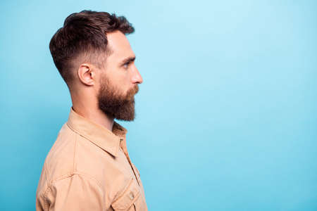 Profile side photo of focused person looking wearing brown shirt isolated over blue background