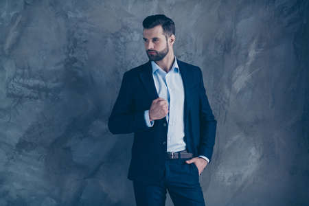 Portrait of gorgeous man touching his jacket look wearing pants trousers formal wear isolated over grey background Фото со стока