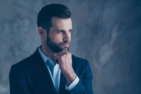 Profile side photo of elegant man with his fingers touching chin looking wearing perfect blazer jacket isolated over gray background Фото со стока