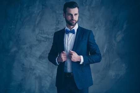 Portrait of gorgeous man touching his jacket looking isolated over gray background