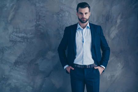 Portrait of gorgeous dreamy entrepreneur looking putting his hands in pocket wearing pants trousers formal wear isolated over grey background