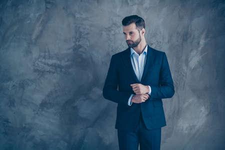 Retrato de hombre hermoso tocando su camisa mirando soñador vistiendo chaqueta blazer aislado sobre fondo gris
