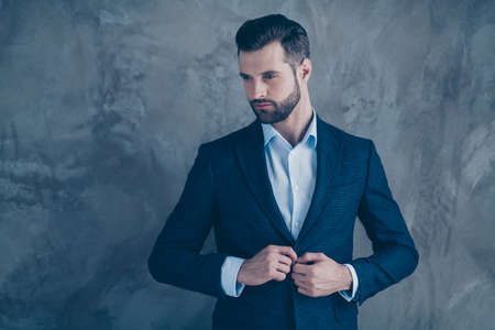 Portrait of magnificent guy touching his jacket looking dreamy isolated over grey background