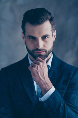 Portrait of elegant pensive man touching his chin looking wearing blazer jacket isolated over grey background Фото со стока