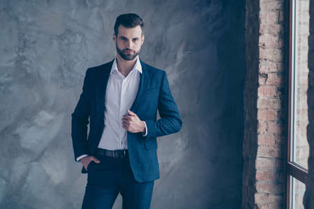 Portrait of minded entrepreneur, looking touching his modern jacket blazer wearing pants trousers shirt isolated over grey background Фото со стока