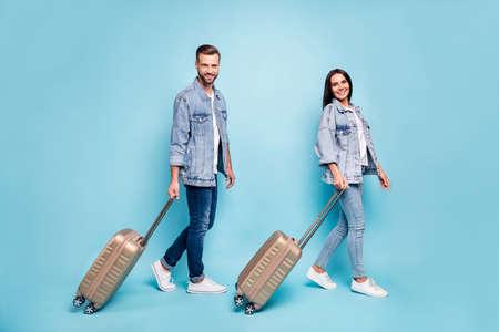 Profilseitenfoto in voller Größe von charmanten Ehepartnern, die Rucksäcke mit Denim-Jeansjacken einzeln auf blauem Hintergrund halten