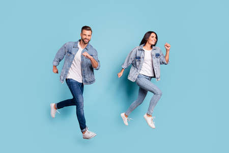 Full length body size photo of beautiful charming gorgeous turned couple with groom fiance running after fiancee while isolated with blue background