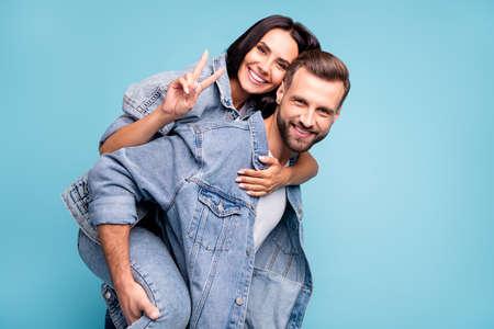 Ritratto di un uomo carino che porta la sua fidanzata facendo segni a V indossando una giacca di jeans denim isolata su sfondo blu Archivio Fotografico