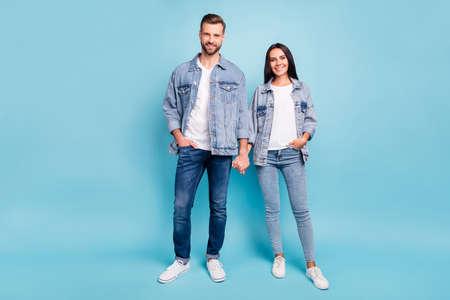 Photo pleine longueur de personnes mignonnes souriantes portant des vestes en jean isolées sur fond bleu
