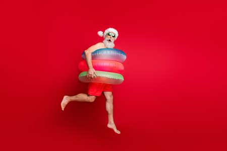 Ganzkörperansicht von hübscher, fröhlicher, fröhlicher, fröhlicher, positiver Comic, kindisch, verspielt, bärtiger, grauhaariger Mann, beeilen Sie sich, isoliert auf hell leuchtend rotem Hintergrund Standard-Bild