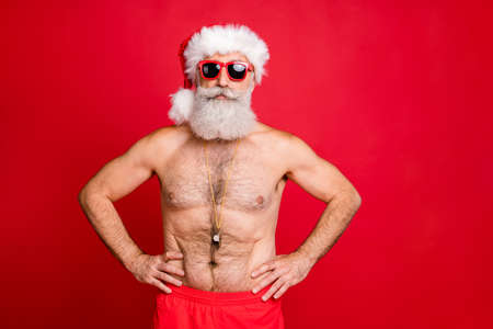 Portrait of his he nice attractive handsome content sporty muscular bearded virile gray-haired macho hands on hips spa resort trip rescue save isolated on bright vivid shine red background