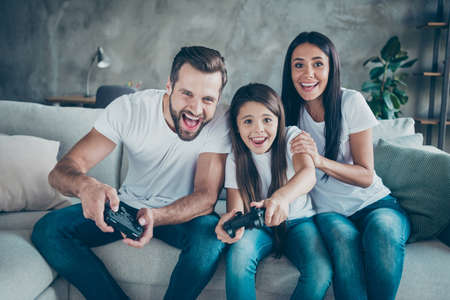 Portrait of nice attractive lovely cheerful cheery funny family fan wearing casual white t-shirts jeans denim sitting on divan having fun video game spending free time indoors