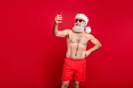 Portrait of his he nice attractive handsome funky cheerful cheery bearded gray-haired man wearing trunks taking making selfie weekend isolated over bright vivid shine red background Stockfoto