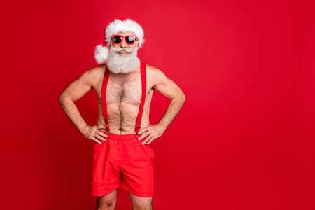 Portrait of hie he nice attractive cheerful content muscular funky gray-haired macho hands on hips holly jolly winter christmastime isolated over bright vivid shine red background